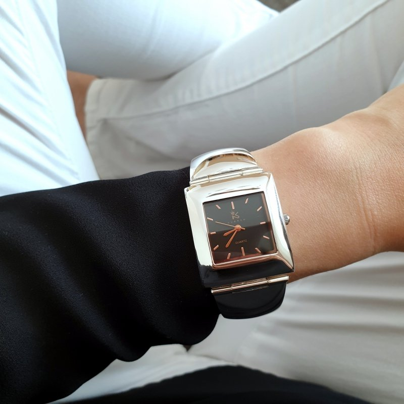 srebrny zegarek z czarną tarczą