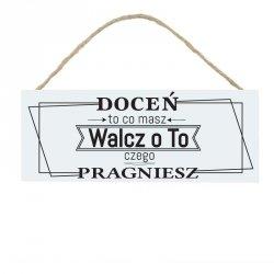 Drewniana tabliczka w kształcie prostokąta z napisem Doceń to co masz...